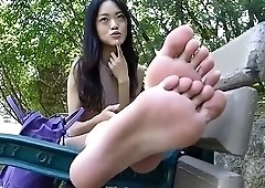 Pretty Oriental babe exposes her lovely feet in the outdoors