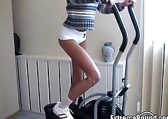 Hot athletic Russian girl tied to the bicycle in the gym