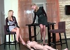 Collared and leashed slave serving two mistresses