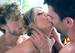 Blonde is kissed and fucked by two men in a hot threesome in front of the fire