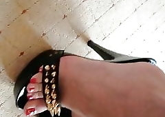 Showing her legs, spiked high heel mules and red long nails.