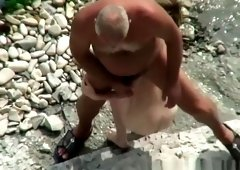Voyeur hidden in the top of the cliff secretly film nudist couple
